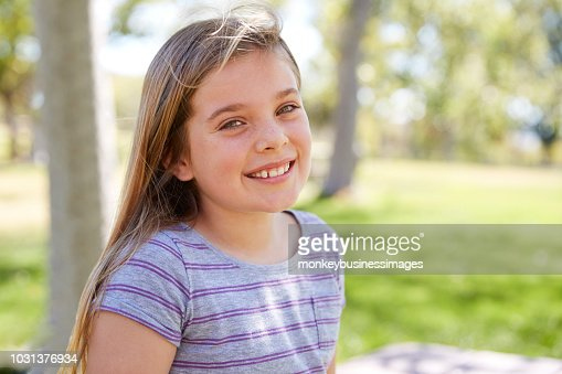 Young smiling schoolgirl looking to camera, close up portrait : Stock Photo