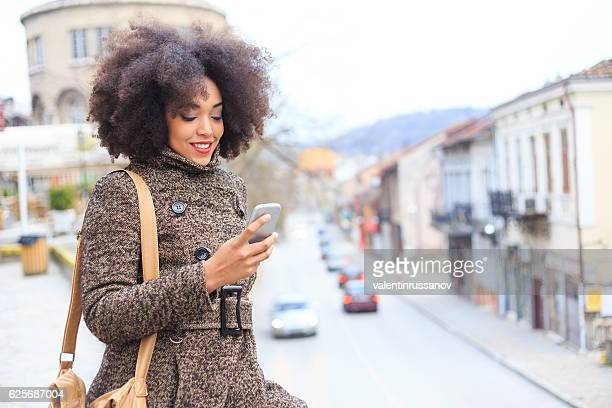 Young smiling tourist using smart phone on street