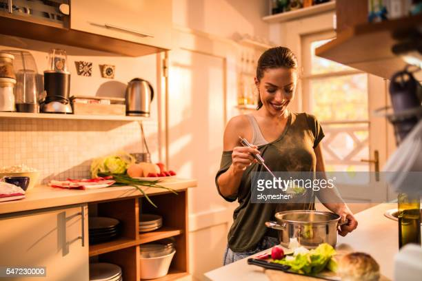 Young smiling woman cooking vegetables in the kitchen.