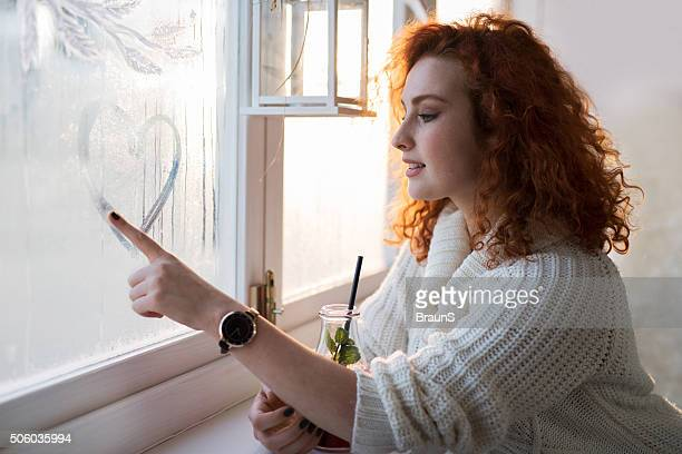 Young smiling woman drawing a heart on a window.