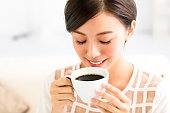 young smiling woman drinking coffee in the morning