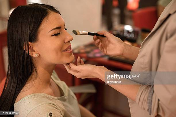 Young smiling woman during make-up treatment.