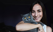 Young smiling woman holding a British shorthair cat on her hands