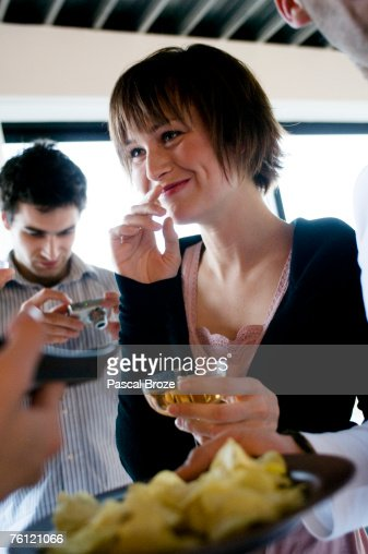 Young smiling woman holding glass of champagne, man with digital camera in  background