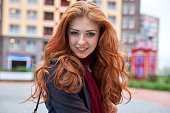 young smiling woman in coat and with long flowing red hair poses for a portrait on a background of urban houses