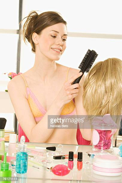 Young smiling woman in underwear brushing wig