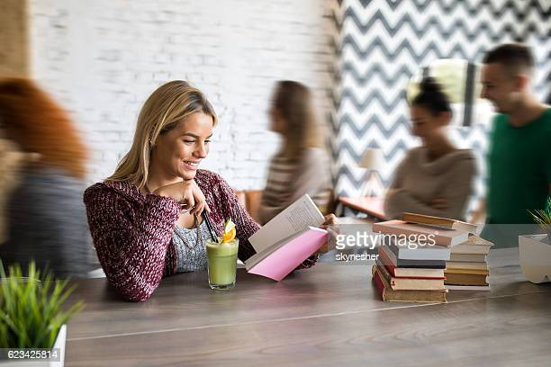 Young smiling woman reading book in cafe.