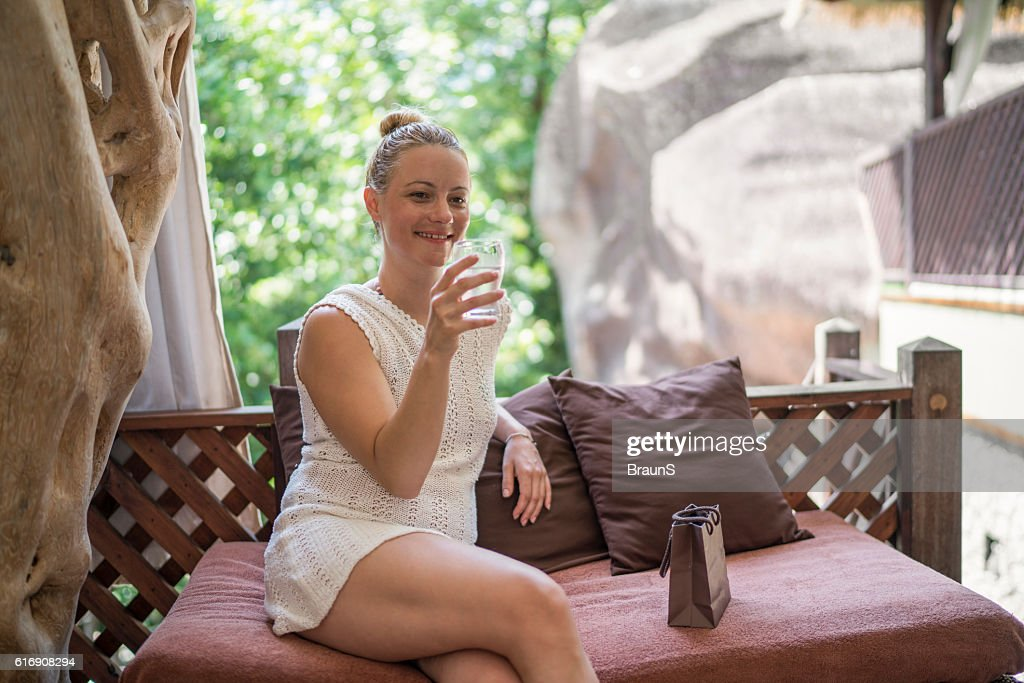 Young smiling woman relaxing outdoors with a glass of water. : Stock Photo