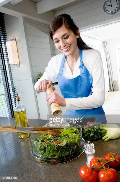 Young smiling woman seasoning a salad