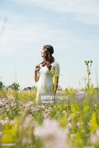 Young smiling woman standing on flower meadow