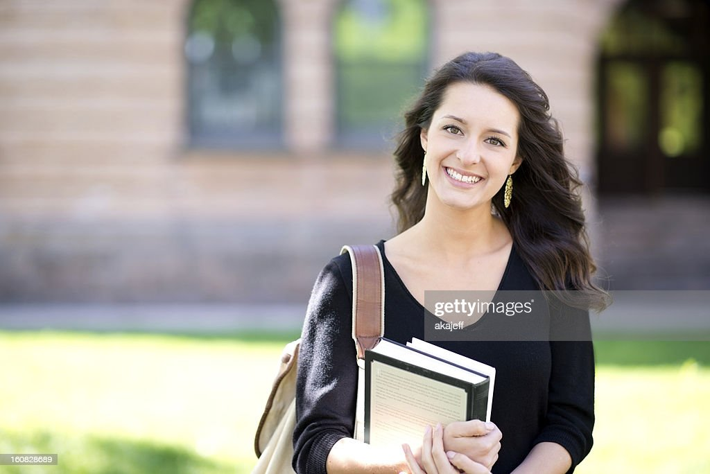 Young smiling woman student holding books : Stock Photo