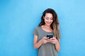 Front portrait of young smiling woman using mobile phone against blue background