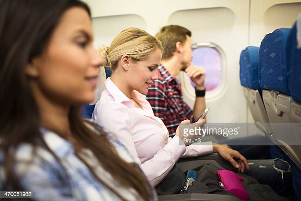 Young smiling woman using smart phone in airplane.