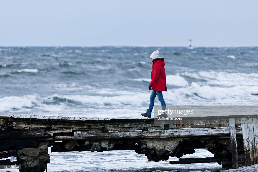Young smiling woman walking on beach : Stock Photo