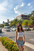 A young smiling woman with a slim athletic figure stands on the street near the road in a tropical country on a sunny day