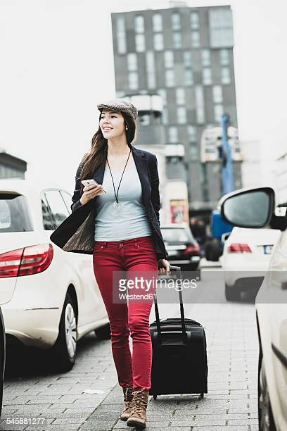 Young smiling woman with smartphone and wheeled luggage