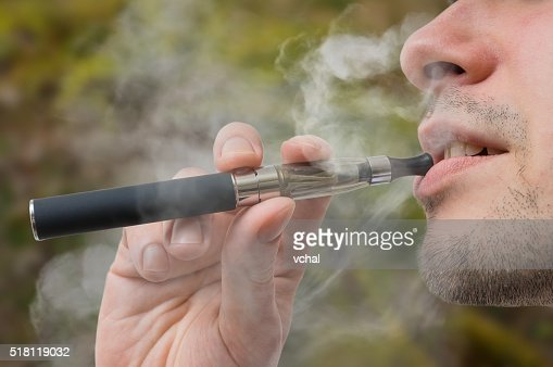 Young smoker is vaping e-cigarette or vaporizer. : Stock Photo