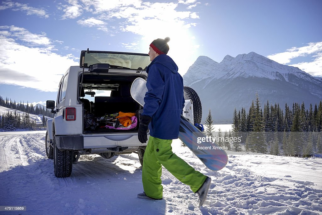 Young snowboarder heads back to vehicle, days end