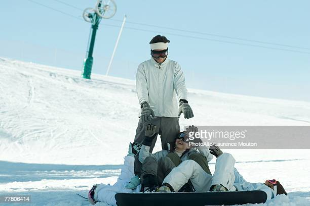 Young snowboarders lying on ground reaching for young man standing behind them
