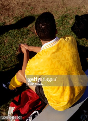 Young soccer play on bench at pitch, rear view