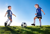 Two Young soccer teammates kicking a ball