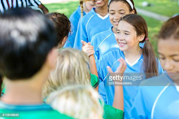 Young soccer team gives high fives after game