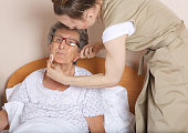 Young social work assistant takes care of a senior woman between 70 and 80 years old. Closeup