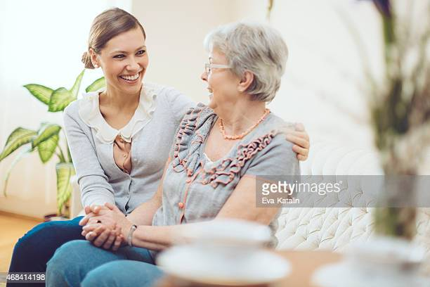 Young social worker is visiting a senior woman at home