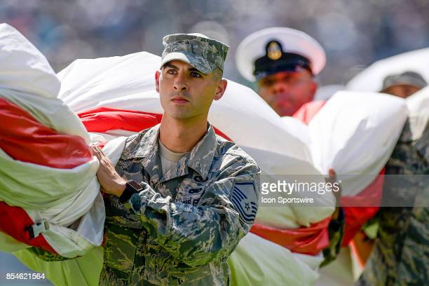 A young soldier carries the flag off the field after the Star Spangled Banner is played during the NFL game between the New York Giants and the...