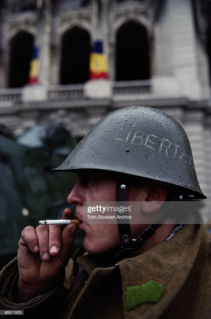 A young soldier in Palace Square, later renamed Revolution Square, in Bucharest during the Romanian Revolution, December 1989. The word 'Libertate' or 'Freedom' is scribbled on his helmet.