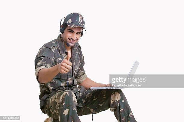 Young soldier using laptop and showing thumbs up sign