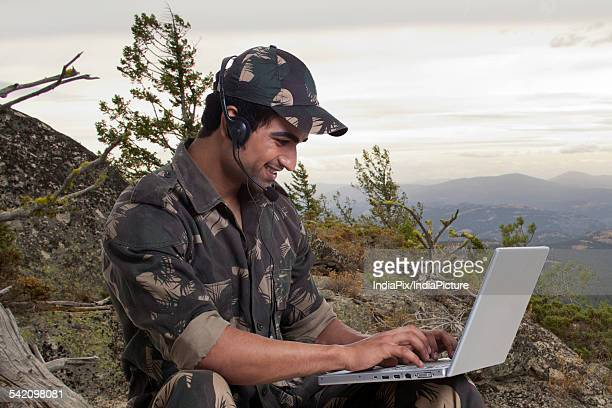 Young soldier using laptop outdoors