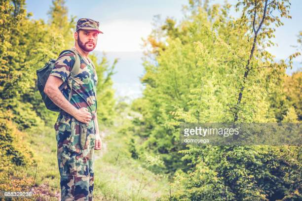 Young soldier walking through forest