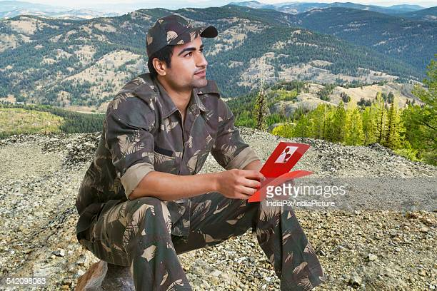 Young soldier with greeting card sitting on rock