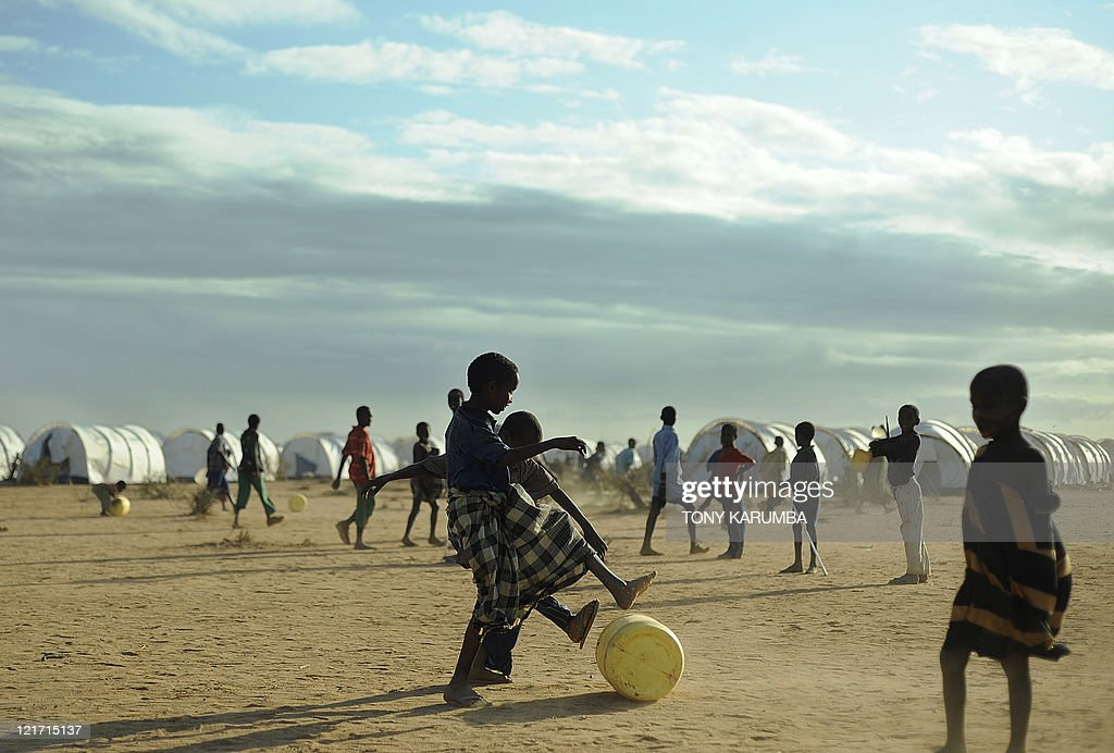 Young Somali refugees roll a jerrycan of water along the ground at the new Ifoextension in Dadaab on July 31 2011 The new site opened to some 5000...