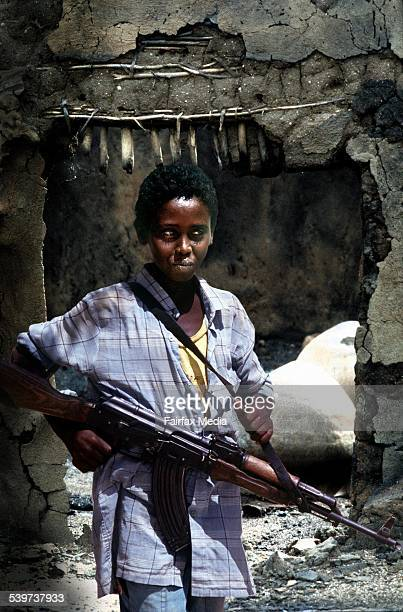 A young Somalian boy with a gun at a ruined home in Somalia Africa 3 July 2001 AFR Picture by GREG NEWINGTON