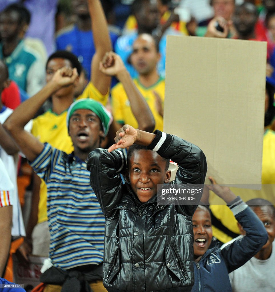 A young South African fan cheers after South Africa beat Spain in a friendly football match at the Soccer City Stadium in Soweto on November 19, 2013. AFP PHOTO / ALEXANDER JOE