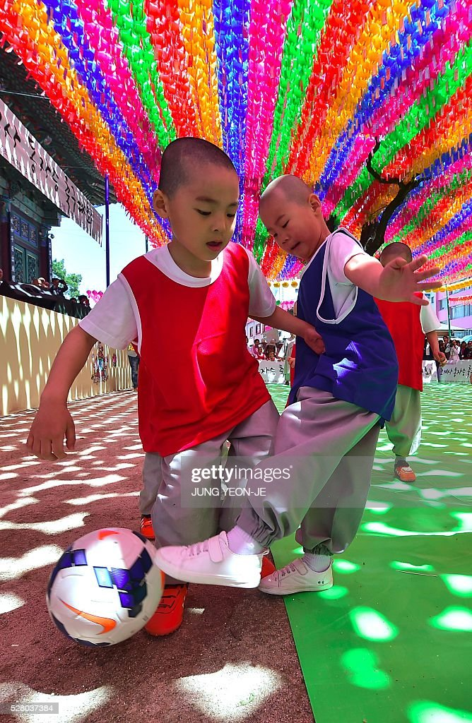 Young South Korean novice monks play football under lotus lanterns during their training program entitled 'Children Becoming Buddhist Monks' at the Jogye Temple in Seoul on May 4, 2016. A special temple-stay program for children to learn about Buddhism, including shaving their heads and wearing monk's robes, continues for two weeks ahead of celebrations for Buddha's birthday on May 14. / AFP / JUNG