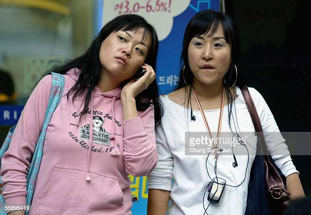 Young South Korean women listen to their mp3 players in the street on October 11 2005 in Seoul South Korea South Korea's Ministry of Information and...