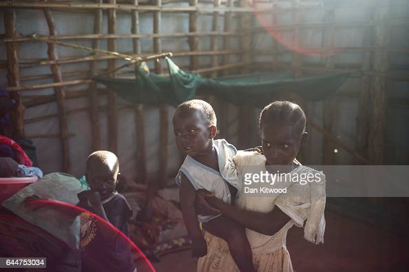 A young South Sudanese girl and her siblings stand in makeshift shelter at the Kerwa Collection point on February 23 2017 in Imvepi Uganda The...