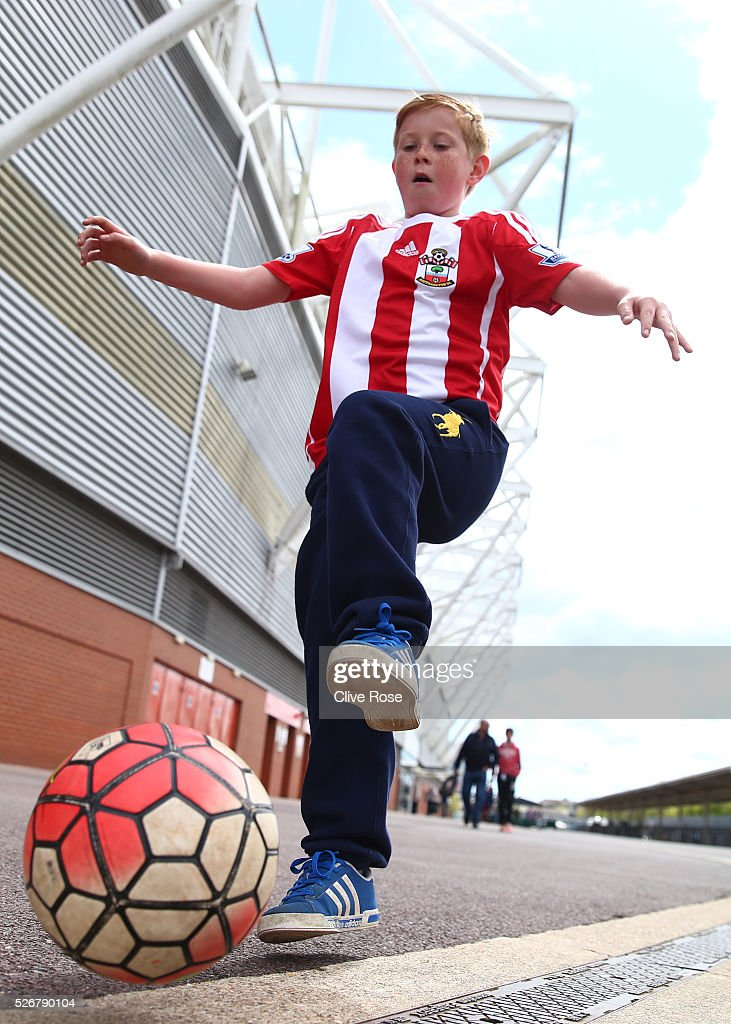 A young Southampton fan kicks a ball about outside the ground prior to the Barclays Premier League match between Southampton and Manchester City at St Mary's Stadium on May 1, 2016 in Southampton, England.