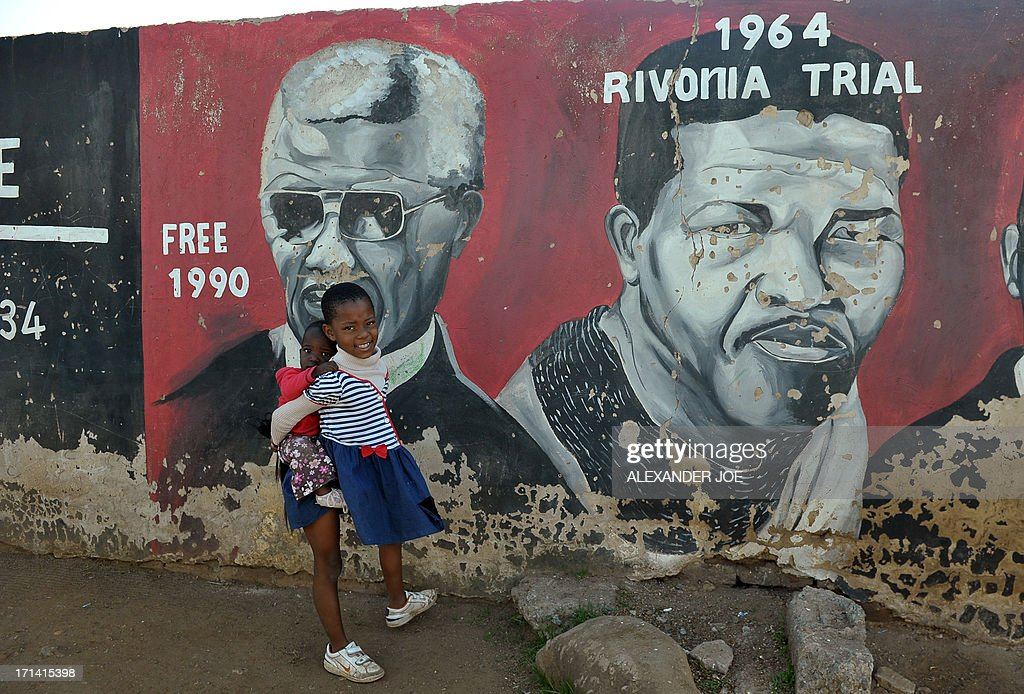 Young Soweto residents are pictured near pantings of anti-apartheid icon Nelson Mandela in Soweto, where Mandela once lived, on June 24, 2013. A statement issued by the South African government reported that former South African president Nelson Mandela's health was in a critical stage after his condition in hospital worsened over the course of 24 hours.
