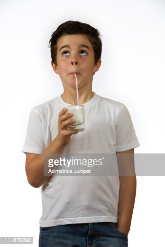 Young Spanish boy drinking milk with a straw : Stock Photo