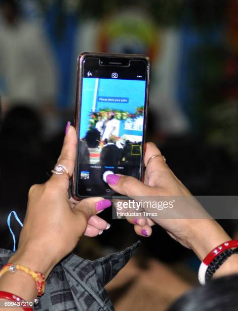 A young spectator films the Indian spiritual leader and founder of the Art of Living Foundation Sri Sri Ravi Shankar during the International Yoga...