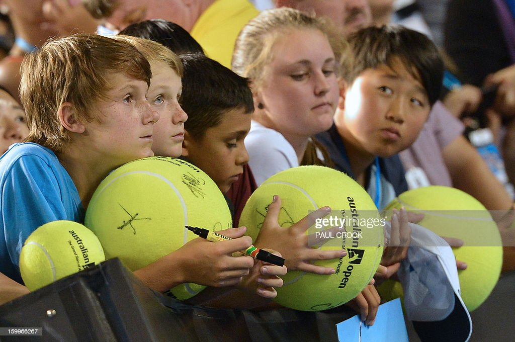 Young spectators wait for Serbia's Novak Djokovic to sign autographs after victory in his men's singles semi-final match against Spain's David Ferrer on the eleventh day of the Australian Open tennis tournament in Melbourne on January 24, 2013. AFP PHOTO/PAUL CROCK IMAGE STRICTLY RESTRICTED TO EDITORIAL USE - STRICTLY NO COMMERCIAL USE