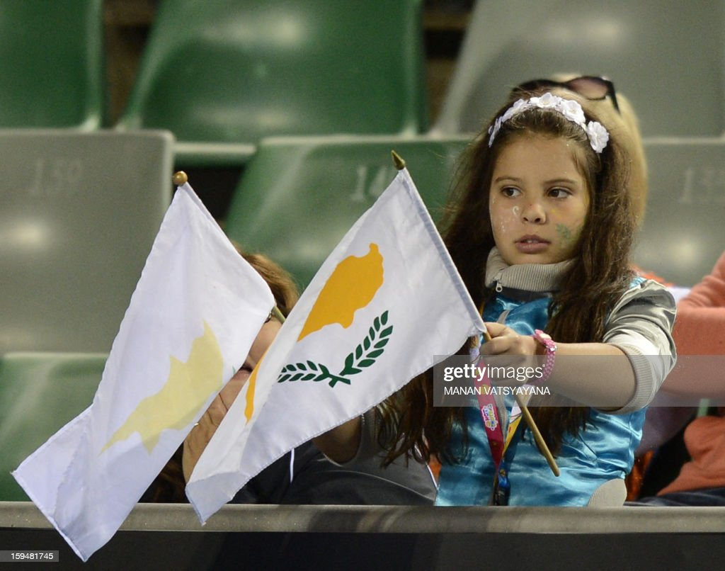 A young spectators waves flags as she cheers for Marcos Baghdatis of Cyprus during his men's singles match against Albert Ramos of Spain on the first day of the Australian Open tennis tournament in Melbourne on January 14, 2013.