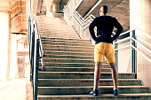 Rearview of a man standing with his hands on his hips at the bottom of a set of stairs while out for a city run. Sport, fitness and healthy lifestyle concept