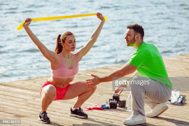 Young sporting woman exercises outdoors with help of personal trainer