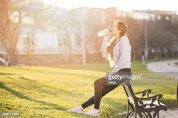 young sportive woman drinking water at sunset