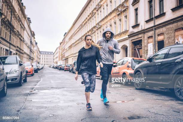 young sports couple running in city streets in cold season
